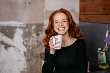 Woman standing in a kitchenette drinking coffee