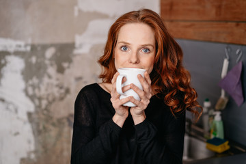 Attractive woman savoring a mug of hot coffee