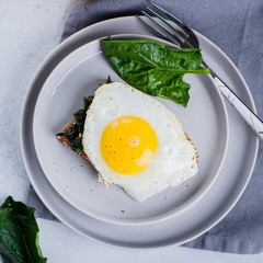 Rye bread toasts with fried spinach and egg with cup of coffee and orange juice on blue table background. Healthy Breakfast Food Concept. Top view with copy space