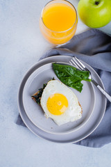Rye bread toasts with fried spinach and egg with glass of orange juice and green apple on blue table background. Healthy Breakfast Food Concept. Top view with copy space