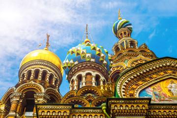 Купола православной церкви, разных форм и цвета, с крестами и изображениями святых, на фоне голубого солнечного неба с облаками