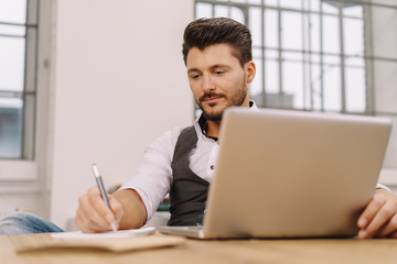 Businessman sitting writing notes at his desk