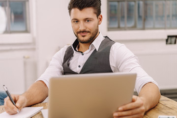 Handsome businessman writing notes
