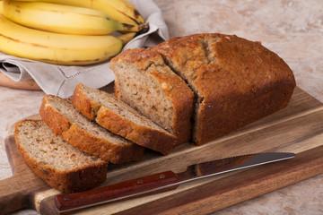 Sliced loaf of banana nut bread on a cutting board