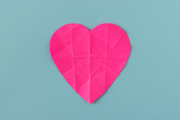 Heart of pink crumpled paper on a bright background. Card with space for text.