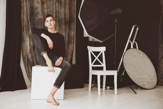 A handsome male model, in a photo studio. On the background of studio equipment. The guy is barefoot, in jeans and a sweater.