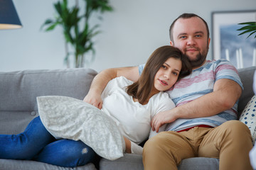 Photo of hugging couple on gray sofa