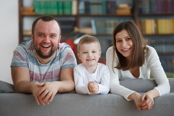 Picture of smiling parents with boys on gray sofa