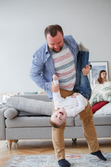 Family picture of man holding son in apartment