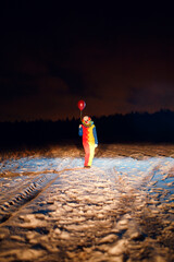Photo from afar in full growth of clown with colorful balloons at night