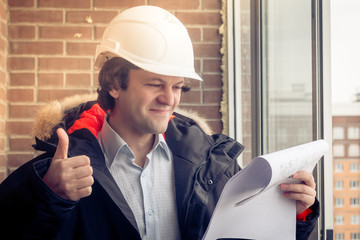 Handsome architect is standing near building outdoors. He is giving thumb up and smiling. The man in helmet is looking at camera happily. Soft focus, toned.