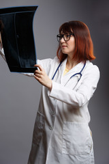 Image of female doctor in glasses and white robe with looking at x-ray on empty gray background