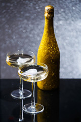Image of bottle of wine and two wine glasses on black table