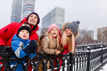 Photo of happy parents with daughter and son on winter walk