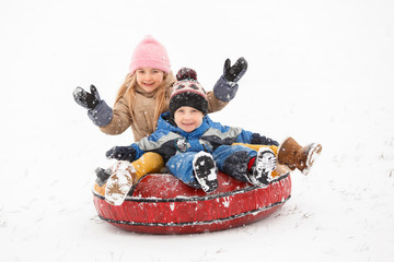 Photo of cheerful girl and boy riding tubing