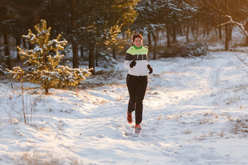 Photo of athlete girl in sneakers on morning run in winter