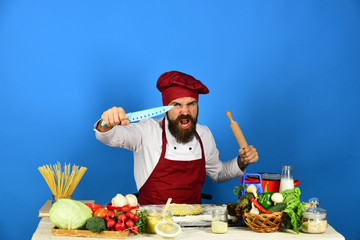 Chef with pasta, vegetables and dough. Cook with angry face