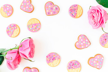 Cookies with pink glaze and roses on white background. Valentines day composition. Flat lay. top view.