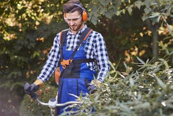 Gardener with goggles and headphones using weedwacker