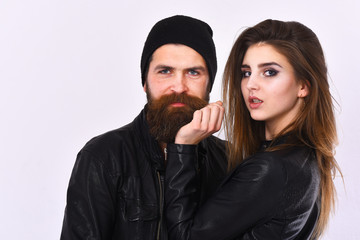 Girl and bearded man in black leather jacket and hat