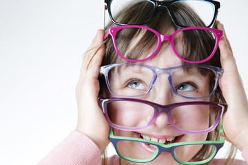 Fototapeta Dziewczynka trzyma kolorowe oprawki okularów.  obraz