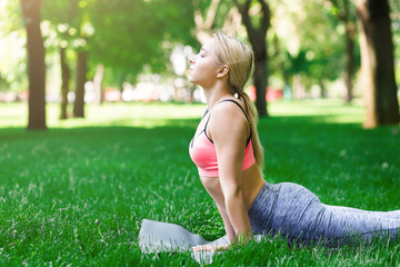 Woman training yoga in cobra pose outdoors