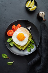 Fried egg with cheese, tomatoes, chard, and waffle with spinach on black ceramic plate on dark concrete background. Sandwich for breakfast. Selective focus. Top view. Copy space.