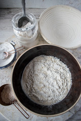mixing flour into yeast in large brown bowl with bread making ingredients around top view