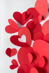 group of hand cut red paper craft hearts on white background