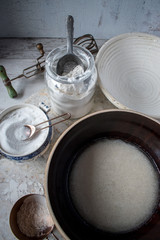 bread making ingredients with fermenting yeast in large brown bowl