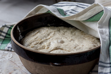 dough rising in large brown bowl covered with tea towel