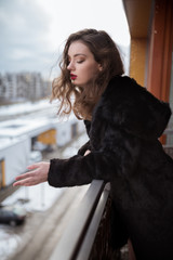young woman in a black fur coat standing on balcony. Melancholy mood