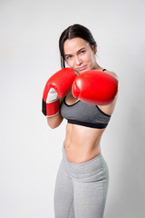 Sporty sexy girl in Boxing gloves on a white background. Direct hit.