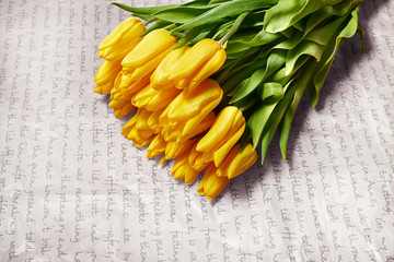 Fresh flower composition, bouquet yellow tulips on craft paper background. Valentine, Women's, 8 march, birthday, mother's day present. Copy space, close up, top view.