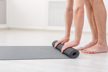 Man rolling his mat after a yoga class