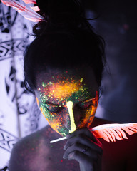 Woman with luminous paint and feather