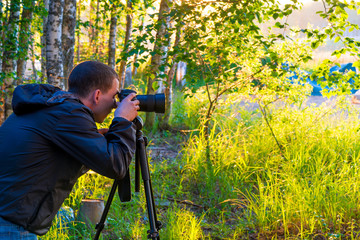 A man with a camera on a tripod takes pictures of nature
