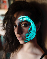 Woman with luminous paint on face