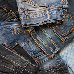 Jeans set of different colors stacked on a background, top view with a copy of the workspace, a concept of a trendy retro style