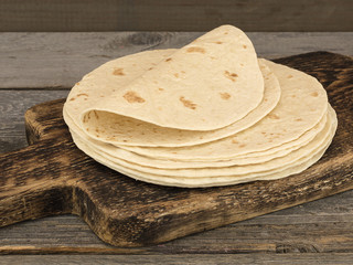 Board with stack of yummy tortillas on wooden table.
