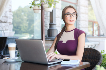 Young businesswoman working with laptop in cafe