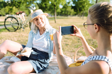 Pleasurable moments. Positive delighted young girl holding a smartphone and smiling while taking a photo of her