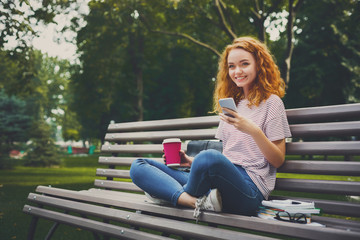 Redhead student girl outdoors chatting on mobile phone
