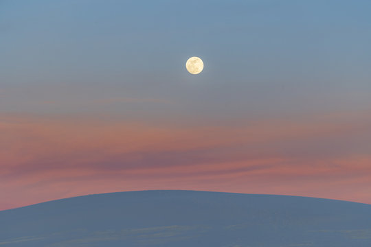 A super moon rises over sand dunes and the remnants of sunset lit clouds