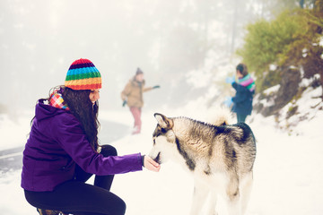 Woman stroking dog in snows
