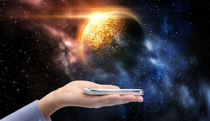 hand holding smartphone over planet in space