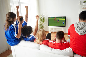 football fans watching soccer game on tv at home