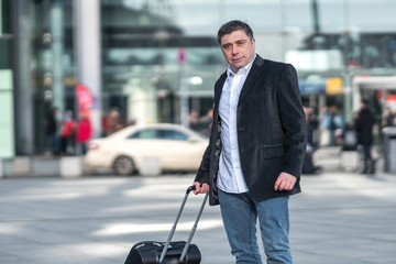 Portrait of traveler with his luggage. Outdoors