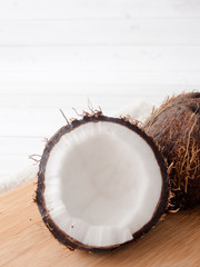 Fresh organic coconut broken into two parts on rustic wooden background