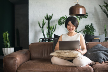 Happy Asian woman using the computer at home.